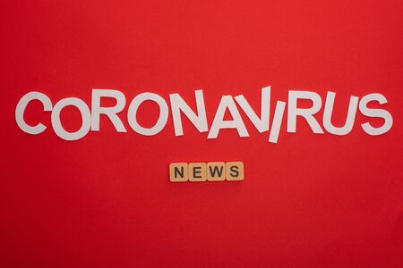 Top view of coronavirus lettering and word news on wooden cubes on red background
