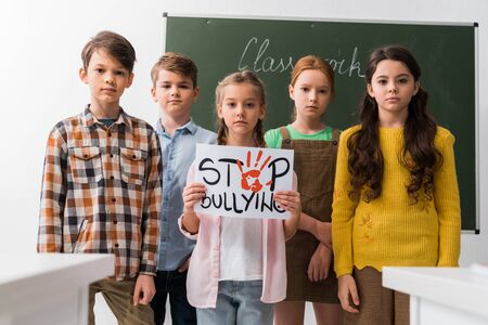 selective focus of schoolkids holding placard with stop bullying lettering