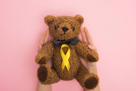 Cropped view of woman holding teddy bear with yellow ribbon on pink background, international childhood cancer day concept