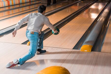 back view of young man throwing bowling ball on skittle alley