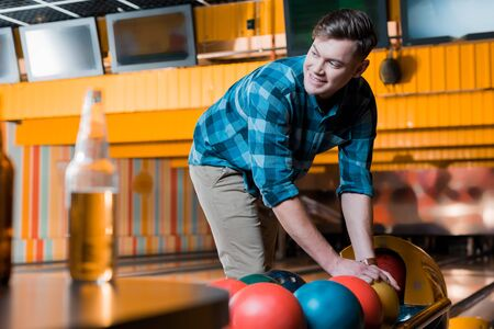 selective focus of handsome smiling man taking bowling ball in bowling club Zdjęcie Seryjne