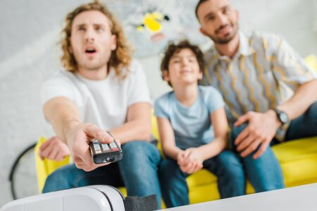 selective focus of parents and mixed race kid watching tv