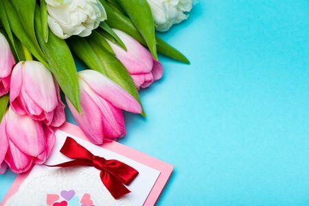 近距离观看郁金香花束附近的贺卡在蓝色的表面