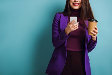 cropped view of smiling girl chatting on smartphone while holding coffee to go on blue background