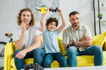 handsome couple playing video game with excited mixed race son