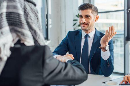 positive multiethnic businessmen shaking hands on meeting