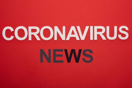 Top view of coronavirus news lettering isolated on red Stock Photo