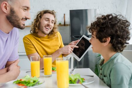 happy homosexual man pointing with finger at digital tablet with blank screen near mixed race son