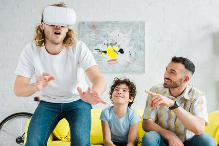 cute mixed race kid near homosexual father pointing with finger at partner in virtual reality headset