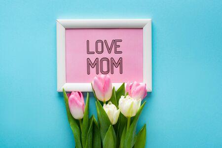 俯视图的郁金香在框架上与我爱妈妈字母在蓝色的背景