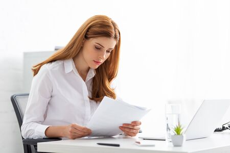 Successful businesswoman holding papers with charts at table in office Banque d'images