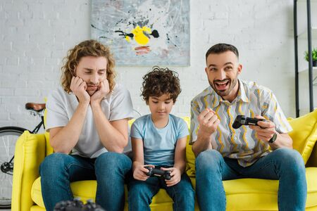 emotional homosexual couple playing video game with upset mixed race son