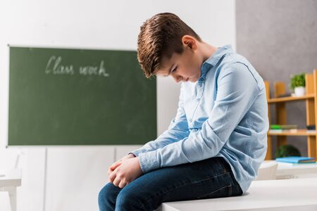 sad and bullied schoolchild sitting on table in classroom