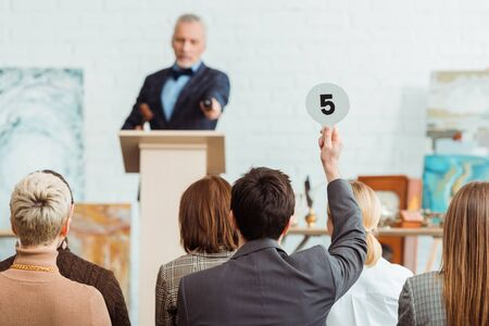 back view of buyer showing auction paddle with number five to auctioneer during auction