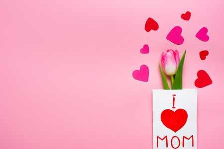 Top view of greeting card with i love mom lettering, tulip and paper hearts on pink background Banco de Imagens