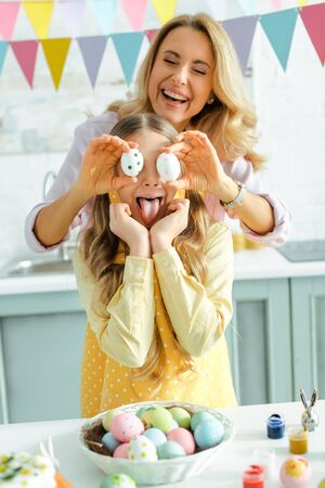 happy mother covering eyes of kid with painted easter eggs