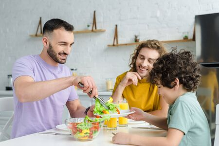 happy man putting salad on plate of mixed race son