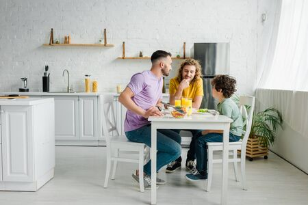 homosexual parents and cute mixed race son having lunch at home