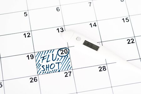 digital thermometer on calendar with marked date and flu shot lettering