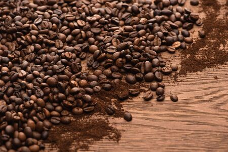 fresh roasted coffee beans and ground coffee on wooden table