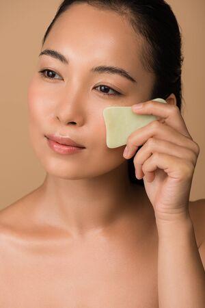 beautiful asian girl using facial gua sha jade board isolated on beige