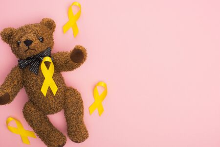 Top view of yellow awareness ribbons and teddy bear on pink background, international childhood cancer day concept