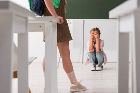selective focus of schoolkid standing near classmate covering face while crying, bullying concept