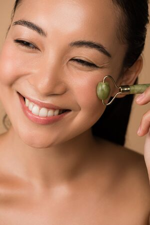 happy beautiful asian girl massaging face with jade roller isolated on beige