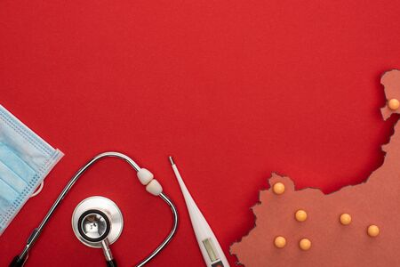 Top view of thermometer, stethoscope, medical mask and layout of china map with yellow push pins on red background Foto de archivo