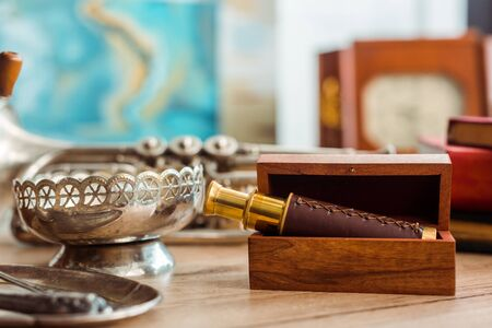 selective focus of spyglass in box and ancient ashtray on table