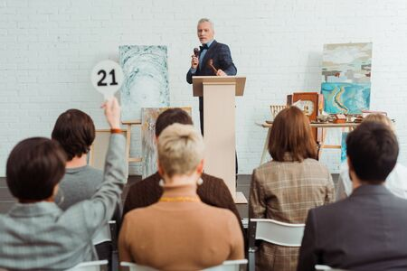 selective focus of auctioneer holding talking with microphone and looking at buyer during auction