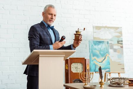 handsome auctioneer in suit pointing with hand at coffee grinder and holding microphone during auction