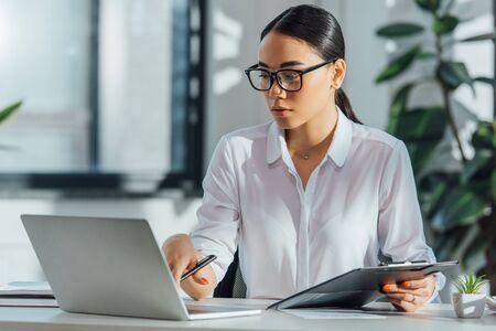 asian translator in eyeglasses working online with laptop in office