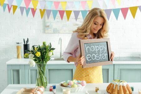 cheerful woman holding chalkboard with happy easter lettering