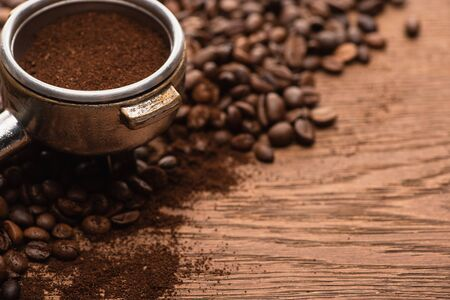 close up view of fresh roasted coffee beans and ground coffee in filter holder on wooden table 스톡 콘텐츠