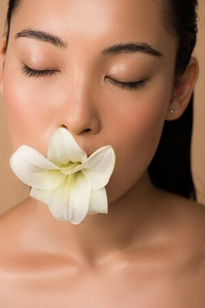 beautiful asian girl with closed eyes holding white lily in mouth isolated on beige