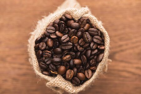 selective focus of fresh roasted coffee beans in sack on wooden surface 스톡 콘텐츠