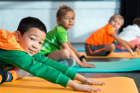 Selective focus of multicultural children with crossed legs stretching on fitness mats