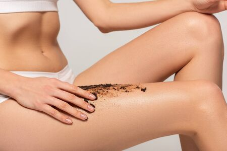 cropped view of girl applying coffee scrub on legs, isolated on grey Foto de archivo