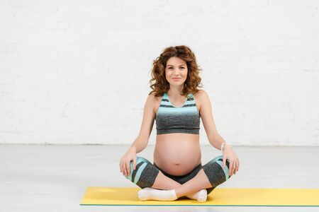 Pregnant girl in sportswear smiling at camera on fitness mat at home