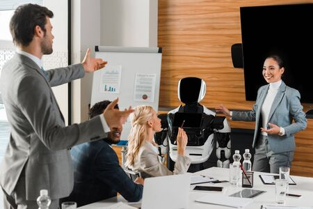 attractive asian businesswoman pointing with hands at robot near colleagues in conference hall Zdjęcie Seryjne