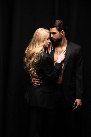 attractive woman hugging handsome man isolated on black