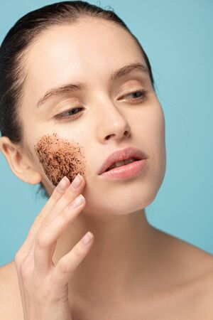 attractive young woman applying coffee scrub on face, isolated on blue