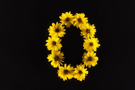top view of yellow daisies arranged in letter O isolated on black