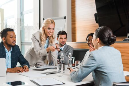 young smiling businesswoman pointing with pencil near multicultural colleagues sitting at desk in conference hall