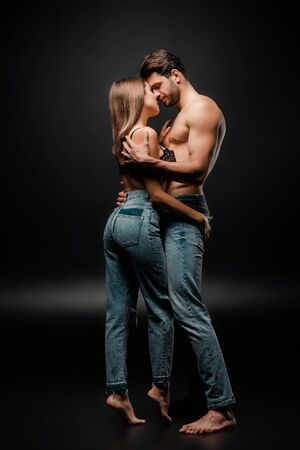 muscular man hugging seductive girl in jeans on black