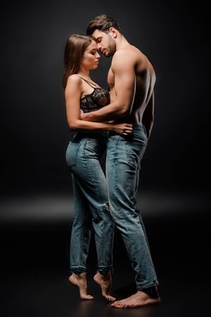 side view of couple in blue jeans standing on black Archivio Fotografico