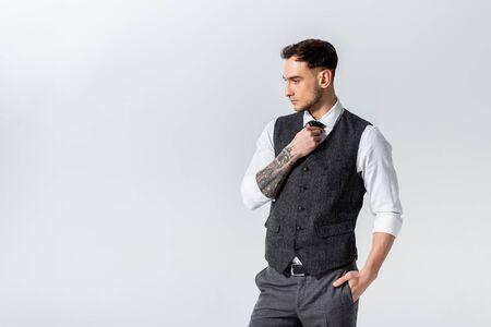 handsome tattooed elegant bridegroom adjusting tie isolated on grey 免版税图像