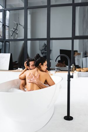 Beautiful naked woman touching handsome boyfriend while taking bath together 免版税图像