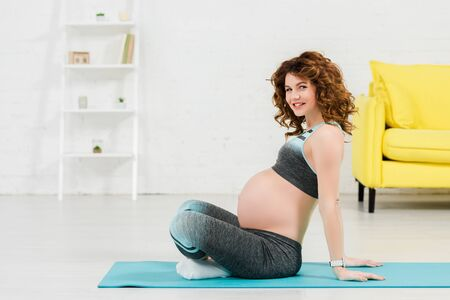 Side view of pregnant woman smiling at camera while exercising on fitness mat in living room
